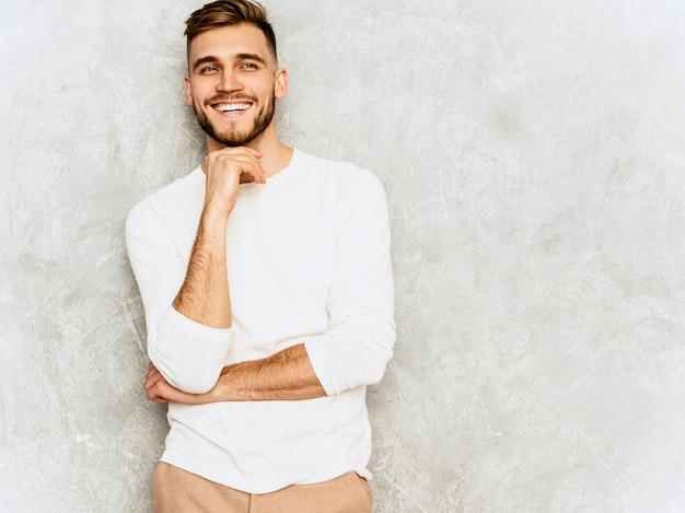 Porträt des hübschen lächelnden hippie-geschäftsmannmodells, das weiße kleidung des zufälligen sommers trägt berühren seines kinns und des denkens