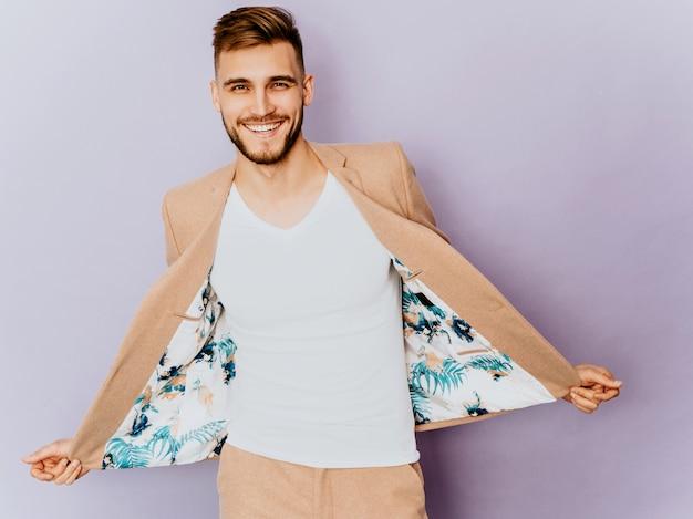 Porträt des hübschen lächelnden hippie-geschäftsmannmodells, das zufälligen beige anzug trägt.