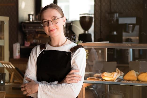 Porträt des hübschen lächelnden inhabers oder der kellnerin der jungen frau im café