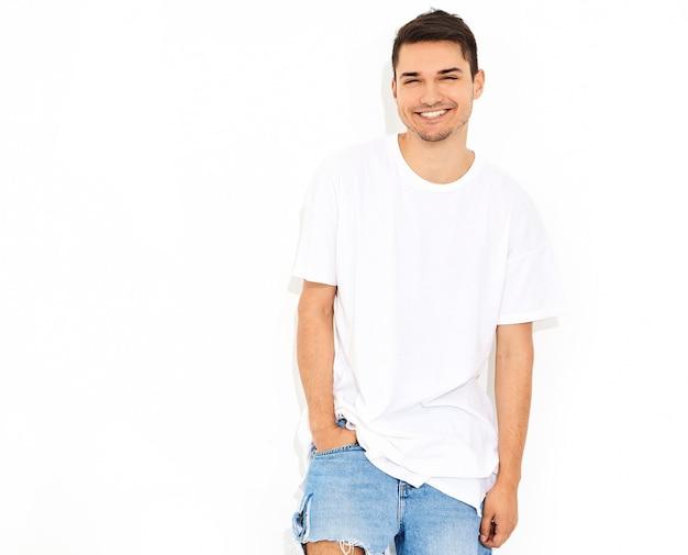 Porträt des hübschen lächelnden jungen vorbildlichen mannes kleidete in der jeanskleidung und in der t-shirt aufstellung an. berührt seinen kopf