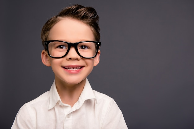 Porträt des hübschen lächelnden kleinen klugen schuljungen in den gläsern