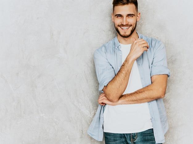 Porträt des hübschen lächelnden modells des jungen mannes, das zufällige hemdkleidung trägt. stilvolle mannaufstellung der mode