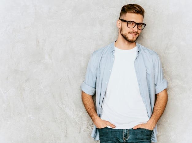 Porträt des hübschen lächelnden modells des jungen mannes, das zufällige hemdkleidung trägt. stilvoller mann der mode, der in den schauspielen aufwirft