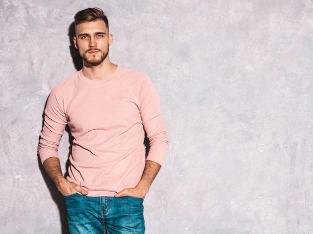 Porträt des hübschen lächelnden modells des jungen mannes, das zufällige sommerrosakleidung trägt. stilvolle mannaufstellung der mode