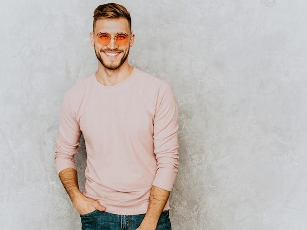 Porträt des hübschen lächelnden modells des jungen mannes, das zufällige sommerrosakleidung trägt. stilvoller mann der mode, der in der runden sonnenbrille aufwirft