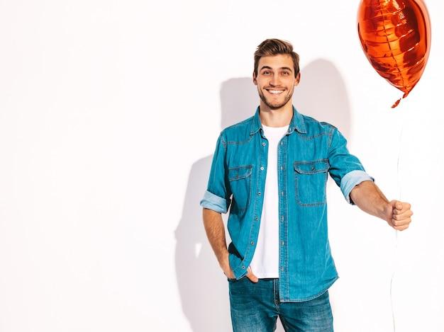 Porträt des hübschen lächelnden stilvollen mannmodells kleidete in der jeanskleidung an. modemann, der geformten ballon des herzens hält.