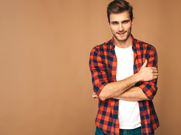 Porträt des hübschen lächelnden stilvollen modells des jungen mannes kleidete im roten karierten hemd an. mode mann posiert. verschränkte arme