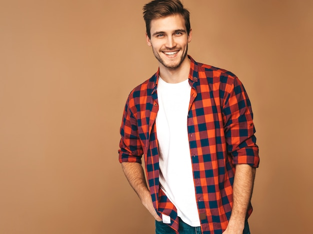 Porträt des hübschen lächelnden stilvollen modells des jungen mannes kleidete im roten karierten hemd an. mode mann posiert