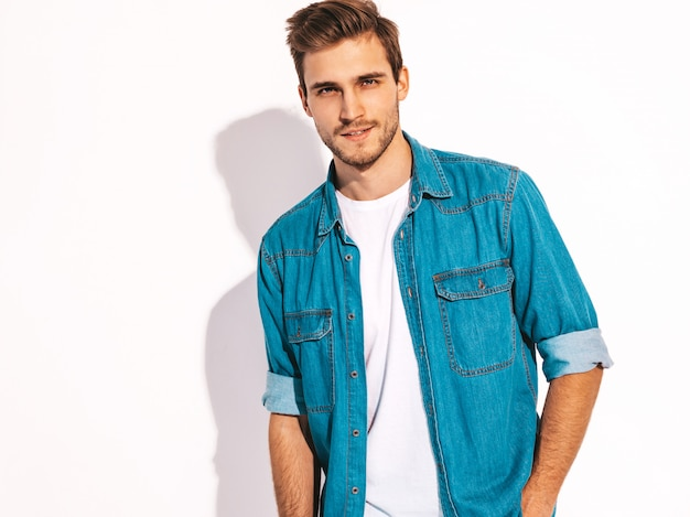 Porträt des hübschen lächelnden stilvollen modells des jungen mannes kleidete in der jeanskleidung an. mode mann