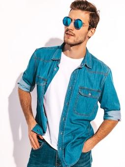 Porträt des hübschen lächelnden stilvollen modells des jungen mannes kleidete in der jeanskleidung an. tragende sonnenbrille des modemannes.
