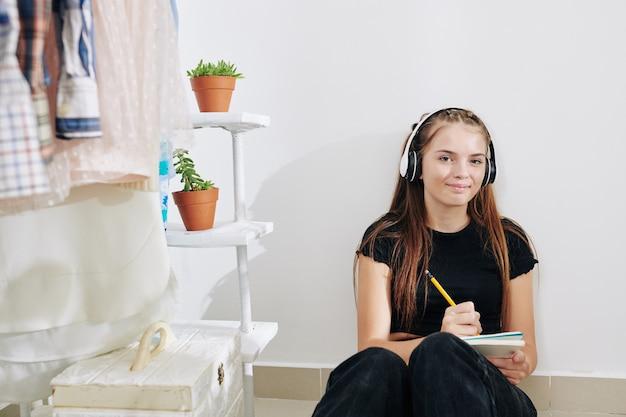 Porträt des hübschen lächelnden teenager-mädchens, das zeit in ihrem zimmer verbringt und kreativen aufsatz in lehrbuch schreibt
