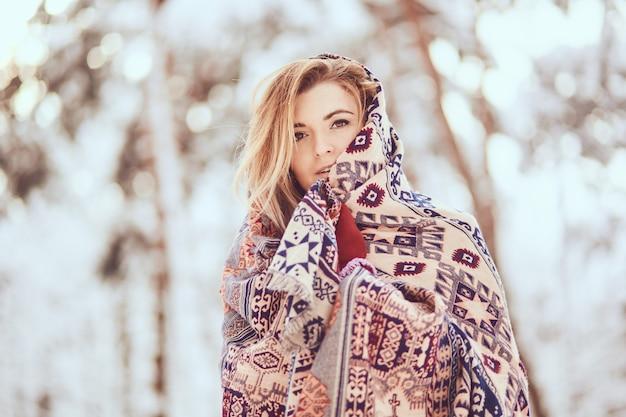 Porträt des hübschen mädchens, das in schal auf einem winterpark einwickelt