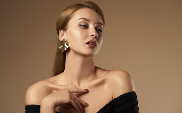 Porträt des hübschen mädchens, das schulterfreies schwarzes kleid und welliges kreatives designohrring auf beigem farbhintergrund trägt.