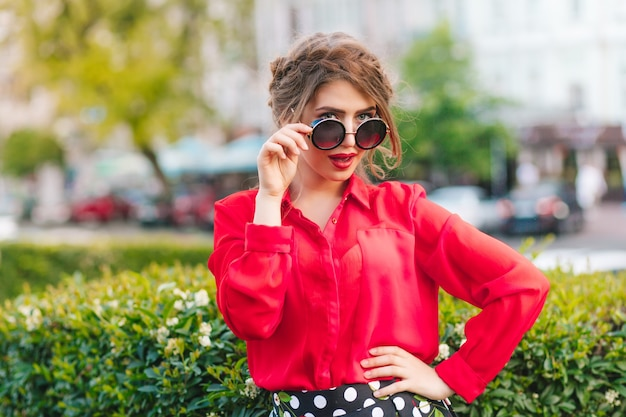 Porträt des hübschen mädchens in der sonnenbrille, die zur kamera im park aufwirft. sie hat frisur, rote bluse.