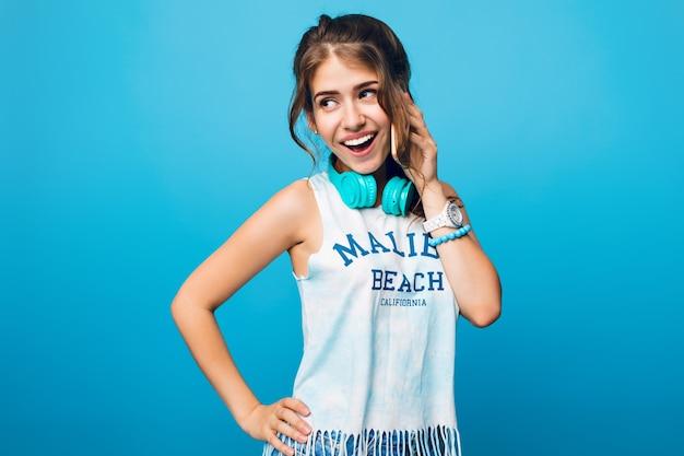 Porträt des hübschen mädchens mit dem langen lockigen haar im schwanz, das am telefon auf blauem hintergrund im studio spricht. sie trägt ein weißes t-shirt und blaue kopfhörer auf den schultern.