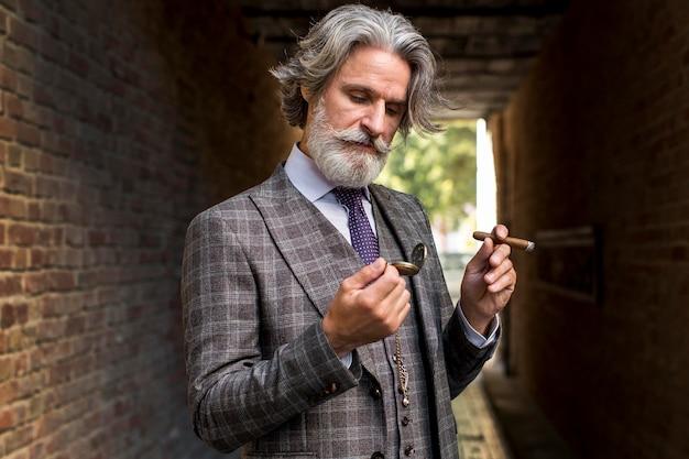 Porträt des hübschen mannes, der mit zigarre aufwirft