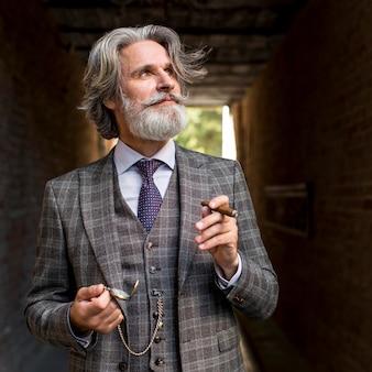 Porträt des hübschen mannes, der zigarre hält