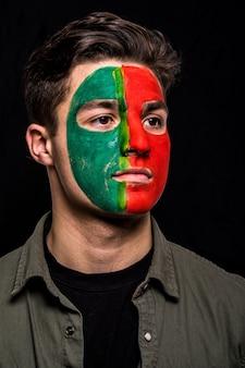 Porträt des hübschen manngesicht-unterstützerfans der portugiesischen nationalmannschaft mit gemaltem flaggengesicht lokalisiert auf schwarzem hintergrund. fans emotionen.