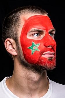 Porträt des hübschen manngesichtsanhängerfans der marokko-nationalmannschaft mit gemaltem flaggengesicht lokalisiert auf schwarzem hintergrund. fans emotionen.