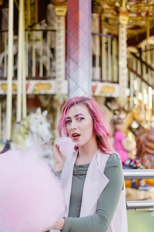 Porträt des hübschen mit rosa haarmädchen mit dem kurzen haarschnitt, der im vergnügungspark auf karussellhintergrund aufwirft. weiblich mit rosa ombre haaren mit pailletten photodyeing haar locken helle glitzer mode