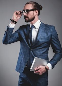 Porträt des hübschen modegeschäftsmannmodells kleidete in der eleganten blauen klage mit gläsern an