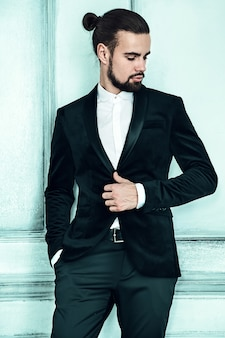 Porträt des hübschen modischen hipster-geschäftsmannmodells der mode, gekleidet im eleganten schwarzen anzug.