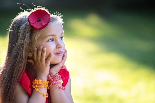 Porträt des hübschen modischen kindermädchens im roten kleid, das warmen sonnigen sommertag genießt.