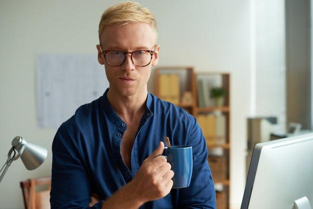 Porträt des hübschen professionellen nachdenkens über idee mit einer tasse tee