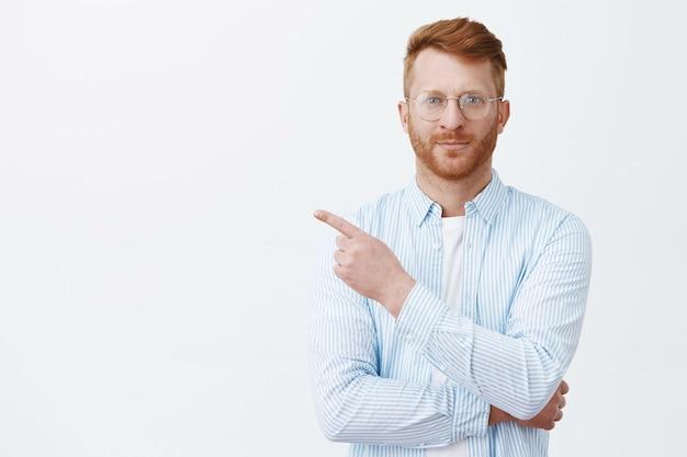 Porträt des hübschen rothaarigen mannes mit bart in der brille und im hemd, die auf obere linke ecke zeigen und lächeln