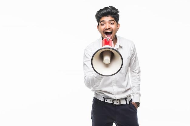 Porträt des hübschen schreiens des jungen mannes unter verwendung des megaphons lokalisiert auf weißer wand