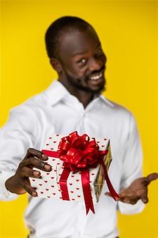Porträt des hübschen schwarzen mit fokus auf einem geschenk