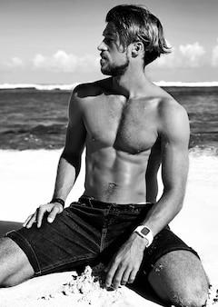 Porträt des hübschen sonnengebadeten modemannmodells, das auf sommerstrand aufwirft