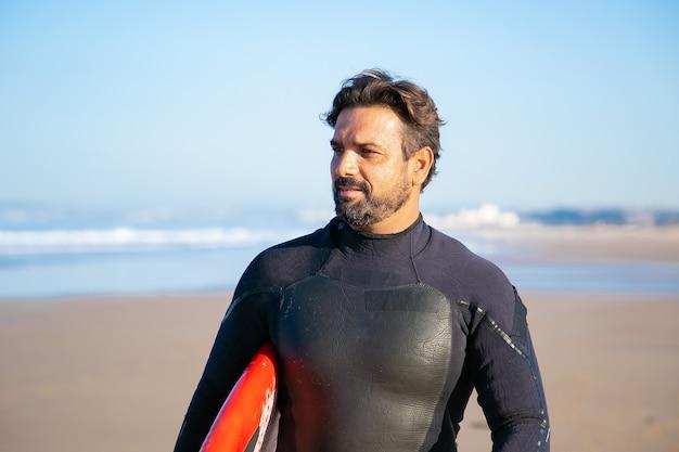 Porträt des hübschen surfers, der am strand mit surfbrett steht und wegschaut
