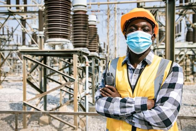 Porträt des hübschen technischen mannes, der walkie-talkie hält und helm vor hochleistungskraftwerk trägt. rückansicht des auftragnehmers auf hintergrund von kraftwerksgebäuden.