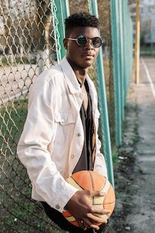 Porträt des hübschen teenagers, der basketballball hält
