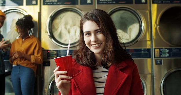 Porträt des hübschen und glücklichen kaukasischen mädchens im roten mantel, das heißen tee oder kaffee mit stroh trinkt, sich ausruht und darauf wartet, dass kleidung gewaschen wird. stilvolle frau nippt getränk im wäscheservice-raum.