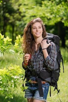 Porträt des hübschen weiblichen touristischen rucksacktouristen in den blättern