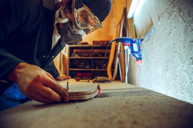 Porträt des hübschen zimmermanns, der mit holzschlittschuh an werkstatt arbeitet