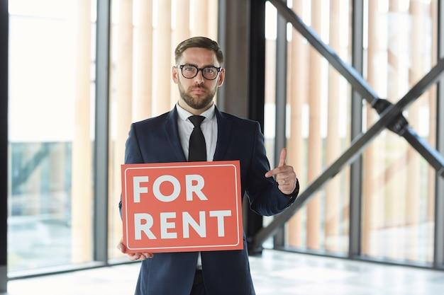 Porträt des immobilienmaklers im anzug, der auf plakat in seinen händen zeigt