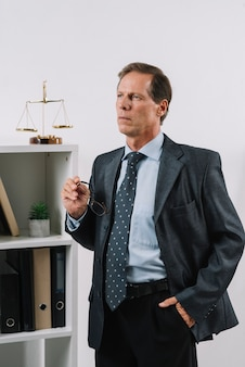 Porträt des in betracht gezogenen reifen rechtsanwalts mit der hand in seiner tasche