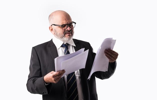 Porträt des indischen asiatischen leitenden geschäftsmannes, der papierdokumente hält oder liest, während er vor weißem hintergrund steht