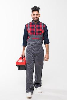 Porträt des indischen mannes, der einen roten werkzeugkasten lokalisiert auf weißem raum hält