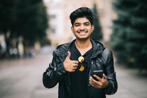 Porträt des indischen mannes im mantel, der nachricht am telefon auf der stadtstraße tippt