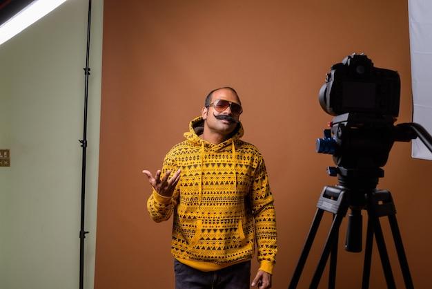 Porträt des indischen mannes mit schnurrbart, der sonnenbrille beim vlogging trägt