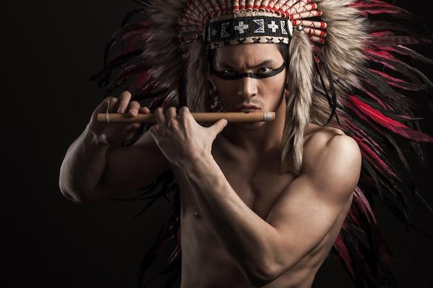 Porträt des indischen starken mannes, der mit traditionellem amerikanischem ureinwohner aufwirft, bilden. flöte spielen