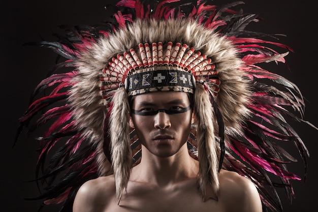 Porträt des indischen starken mannes, der mit traditionellem amerikanischem ureinwohner aufwirft, bilden