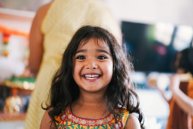 Porträt des indischen weiblichen kindes, das sari-kleid trägt - südasiatisches kind, das spaß am lächeln hat - kindheit, verschiedene kulturen und lebensstilkonzept - fokus auf nase