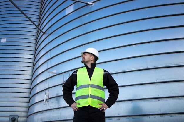 Porträt des industriearbeiters, der durch metallsilo-lagertank steht