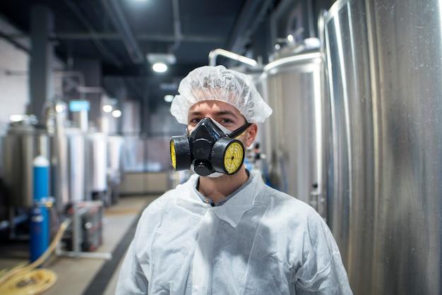 Porträt des industriearbeiters, der schutzuniform und gasmaske trägt