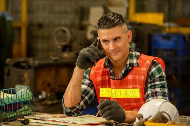 Porträt des ingenieurs, der ein mobiltelefon verwendet, smart engineering, das am telefon spricht und in der fabrik arbeitet, happy teamwork-konzept.